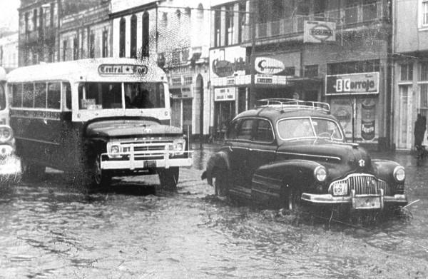 Microbus en medio de calle anegada, c. 1960.