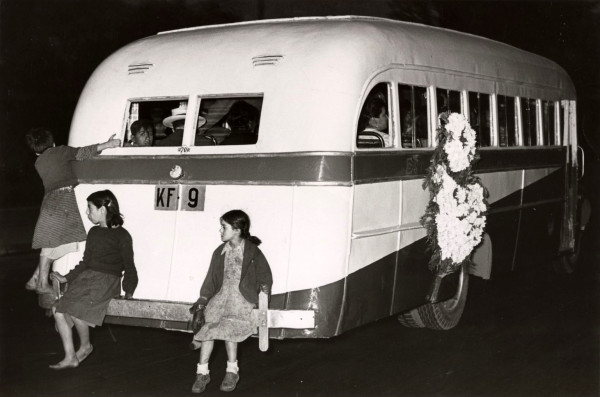 Niñas viajando en parachoque de góndola con corona de flores mortuoria, c.1960.
